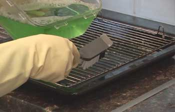 Image of a hand cleaning a grill.